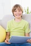Happy boy using digital tablet on sofa Royalty Free Stock Photography