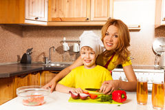 Happy boy using toque cuts vegetables with mother Stock Photos