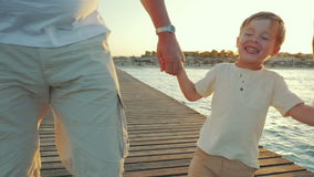 Happy boy walking with grandparents along the pier stock footage