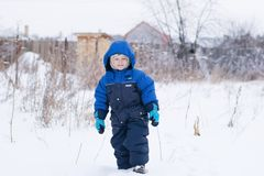 Happy boy walking in a snow stock photography
