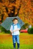 Happy boy walking under an autumn rain Royalty Free Stock Photography
