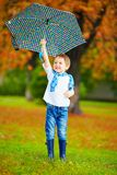 Happy boy walking under an autumn rain royalty free stock photos
