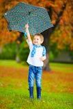 Happy boy walking under an autumn rain Royalty Free Stock Photos