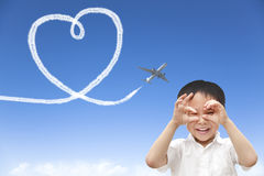 Happy boy watching airplane flying and drawing a heart of cloud Stock Photos