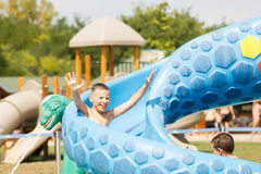 Happy boy on water slide Stock Images
