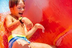 A happy boy on water slide in a swimming pool having fun during summer vacation in a beautiful aqua park. A boy. A happy boy on water slide in a swimming pool stock photography