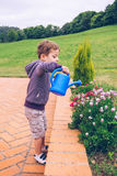 Happy boy watering flowers in the garden Royalty Free Stock Photo