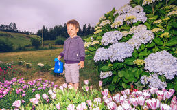 Happy boy watering flowers in the garden Royalty Free Stock Photos