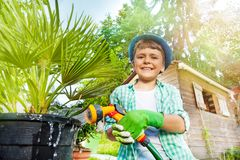 Happy Boy Watering Palm Tree Using Hand Sprinkler Royalty Free Stock Photo