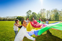Happy boy waving colorful parachute with friends. Portrait of happy African boy waving colorful parachute full of little balls with her friends at sunny day Royalty Free Stock Images