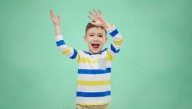 Happy boy waving hands over green school board Stock Image