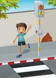 A happy boy waving his hand near the pedestrian lane Stock Photo
