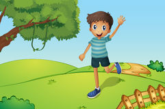 A happy boy waving while running in the hill Royalty Free Stock Photography
