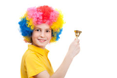 Happy boy wears colorful wig and calls by hand bell. Isolated on white background Stock Images