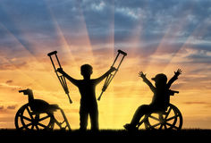Happy boy in wheelchair and boy standing with crutches disabled person sunset Royalty Free Stock Photography
