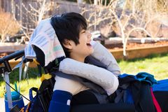 Happy boy in wheelchair outdoors smiling and laughing royalty free stock photo