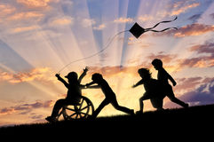 Happy boy in wheelchair playing with children and kite. Sunset. Concept happy child disabled Stock Images