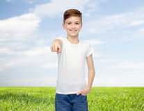 Happy boy in white t-shirt pointing finger to you. Childhood, fashion, advertisement and people concept - happy boy in white t-shirt and jeans pointing finger to Stock Images