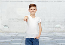 Happy boy in white t-shirt pointing finger to you. Childhood, fashion, advertisement and people concept - happy boy in white t-shirt and jeans pointing finger to Stock Photography