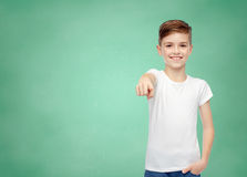 Happy boy in white t-shirt pointing finger to you. Childhood, school, education, advertisement and people concept - happy student boy in white t-shirt and jeans Stock Photography