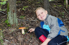 The happy boy who has found a mushroom Stock Image
