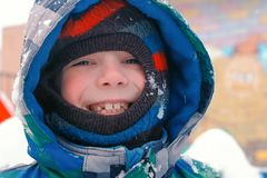 Happy boy in winter clothes smiling looking at camera during snowfall. royalty free stock images