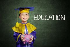 Happy Boy With Scholar Gown And Piggy Bank Stock Photography