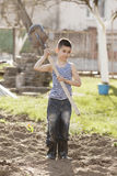 Happy boy working with shovel in garden Royalty Free Stock Photo