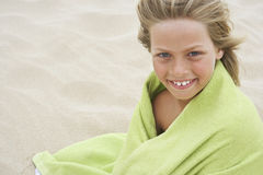Happy Boy Wrapped In Towel Sitting On Beach Stock Photo
