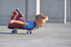 Happy boy, 5 years old, playing with a skateboard royalty free stock photography