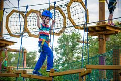 Happy boy on the zip line. proud of his courage the child in the. High wire park. HDR Royalty Free Stock Photos