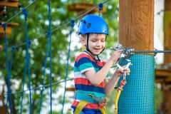 Happy boy on the zip line. proud of his courage the child in the. High wire park. HDR Royalty Free Stock Photo