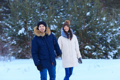 Happy boyfriend and girlfriend holds hands. In winter forest. Love relationship. Selective Focus royalty free stock photo
