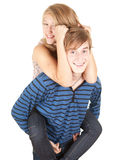 Happy boyfriend giving girl a piggyback Royalty Free Stock Photos