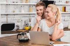 Happy boyfriend hugging girlfriend in kitchen while she. Using laptop royalty free stock photo