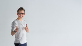 Happy boyfriend show sight thumbs up and good luck. Portrait of a smiling casual spectacled man showing two thumbs up and looking at camera over gray background Stock Image