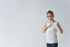 Happy boyfriend show sight thumbs up and good luck. Portrait of a smiling casual spectacled man showing two thumbs up and looking at camera over gray background Stock Photo