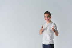 Happy boyfriend show sight thumbs up and good luck. Portrait of a smiling casual spectacled man showing two thumbs up and looking at camera over gray background Stock Photography