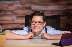 Happy Boyish Boss at Desk Royalty Free Stock Photography