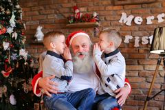 Happy boys brothers simultaneously whisper in ear of Christmas royalty free stock photos