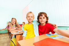 Happy boys cuddle and sit together in school Stock Images