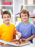 Happy boys cutting pizza Royalty Free Stock Photos