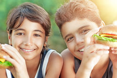 Happy boys eating burgers. Portrait of a two happy boys eating hamburgers outdoors, cheerful teens enjoying unhealthy but delicious food, picnic on sunny day Stock Images