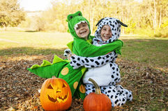 Happy boys hugging Autumn   costumes hug and smile by pumpkins Stock Images