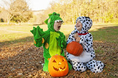 Happy boys in Autumn Halloween costumes sit by pumpkins Royalty Free Stock Photography