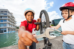 Happy boys fixing bike together outdoors in summer Royalty Free Stock Image