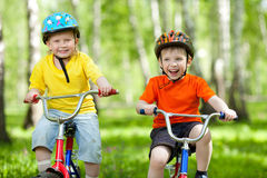 Happy boys friends on bicycle in green park Royalty Free Stock Photo