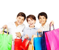 Happy boys with gifts. Kids carrying colorful shopping bags with Christmas presents isolated over white background, holidays Stock Image