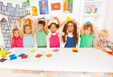 Happy boys and girls in the kindergarten art class. Kindergarten group of little kids, boys and girls diverse looking holding cardboard shapes by the table in stock photography