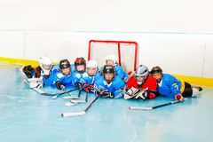 Happy boys and girls laying on ice hockey rink royalty free stock photography